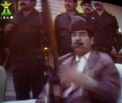sadam-with-rifle-iraqi-tv.jpg